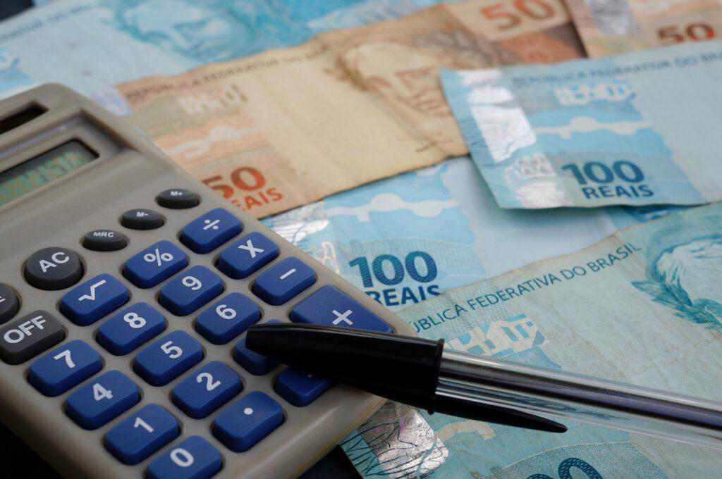 Calculadora e notas de dinheiro, representando a PEC dos precatórios